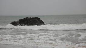 onweer De golven breken grote rotsen stock video