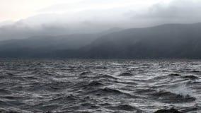 Onweer op achtergrond van grijze wolken in hemel en zwart donker water van Meer Baikal stock footage