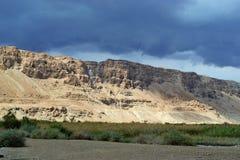 Onweer over berg Masada in Judean-woestijn, Israël donkerblauwe hemel boven de berg naast dode overzees stock fotografie