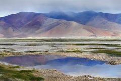 Onweersbui bij het hooggebergte van het Tso Kara meer: lilac wolken dalen aan de bergen, de kalme oppervlakte van het meer refle Stock Afbeeldingen