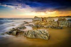 Onweersbui het brouwen over grote rotsen op het strand Stock Afbeelding