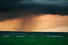Onweerswolk met regen bij zonsondergang, boven het dorp Stock Afbeeldingen