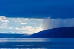 Onweerswolk over meer Baikal met zonlicht en regen Bergen in de mist, golven op het water, wolken en blauwe tonen van stock foto's