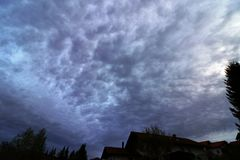 Onweerswolken in de avond hemel boven een stad Stock Afbeelding