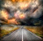 Onweerswolken en bliksem over weg Stock Foto