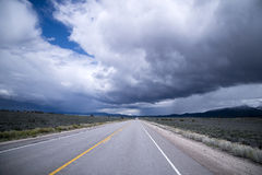 Onweerswolken en eindeloze staightweg in Nevada Stock Foto's