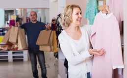 Żony kupienia suknia przy odzież sklepem, mężczyzna zanudza zdjęcie stock