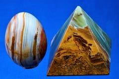 Onyx ist ein wertvolles und extrem schönes Mineral, eine Pyramide und ein Ei auf einem blauen Hintergrund stockfotos