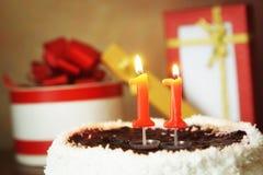 Onze anos de aniversário Bolo com velas e os presentes ardentes Imagem de Stock