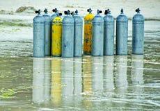 Onze réservoirs d'air de scaphandre se reposant sur une plage humide image stock