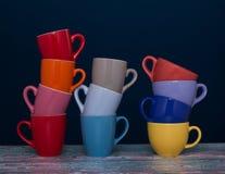 Onze tasses de café de différentes couleurs dans trois groupes Image libre de droits