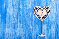 Ooden hjärta sned på en blå träbakgrund Arkivfoto