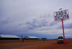 Oodnadatta Roadhouse. The road and beckoning sign at the iconic and popular Pink Roadhouse in the very remote town on Oodnadatta in Australia`s Simpson Desert royalty free stock photography