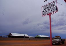 Oodnadatta Roadhouse. The road and beckoning sign at the iconic and popular Pink Roadhouse in the very remote town on Oodnadatta in Australia`s Simpson Desert stock photography