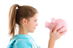 Oog-aan-oog - geïsoleerd meisje met spaarvarken op wit Royalty-vrije Stock Afbeeldingen