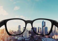 Oogglazen die aan stadsmening kijken die, op glazenlens wordt geconcentreerd royalty-vrije stock afbeeldingen