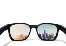 Oogglazen die aan stadsmening kijken die, op glazenlens wordt geconcentreerd stock foto