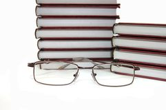 Oogglazen die over boeken leggen Stock Afbeelding
