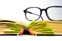 Oogglazen en boek Stock Foto