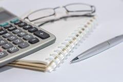 Oogglazen en Calculator op boek Royalty-vrije Stock Foto's