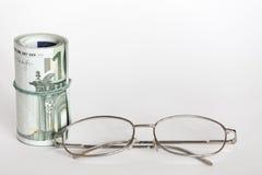 Oogglazen en geld Stock Foto's