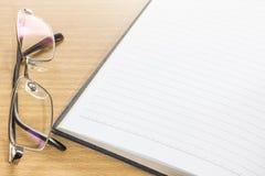 Oogglazen en open notaboek met blanco pagina Royalty-vrije Stock Fotografie