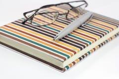 Oogglazen en pen op notitieboekje Royalty-vrije Stock Foto