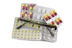 Oogglazen en pillen op witte achtergrond worden geïsoleerd die Stock Foto's