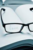 Oogglazen en woordliefde in een notitieboekje, in duotone Stock Fotografie