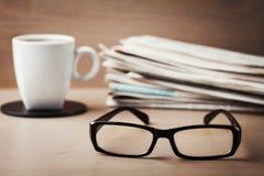 Oogglazen, koffiemok en stapel kranten op houten bureau voor thema's van oftalmologie, slechte visie en lezing Stock Foto