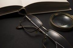 Oogglazen met vergrootglas op donkere oppervlakte met boeken Stock Fotografie
