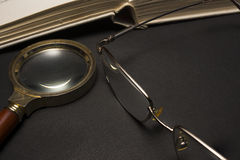 Oogglazen met vergrootglas op donkere oppervlakte met boeken Stock Afbeelding
