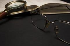 Oogglazen met vergrootglas op donkere oppervlakte met boeken Royalty-vrije Stock Afbeelding