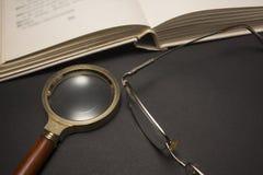 Oogglazen met vergrootglas op donkere oppervlakte met boeken Royalty-vrije Stock Fotografie