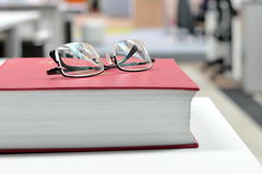 Oogglazen op boek Stock Afbeeldingen