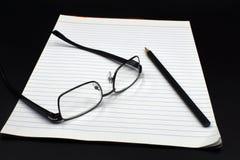 Oogglazen op een blocnote met een potlood en een zwarte achtergrond royalty-vrije stock foto