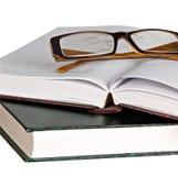 Oogglazen op open boek Stock Afbeelding