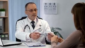 Oogonderzoek, oftalmoloog die oogglazen geven aan vrouwelijke patiënt, controle royalty-vrije stock afbeelding