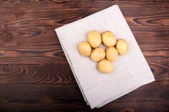 Oogstaardappels in een grijze stof op de donkere houten achtergrond Organische en ongekookte nieuwe lichtbruine aardappels Verse  Stock Afbeelding