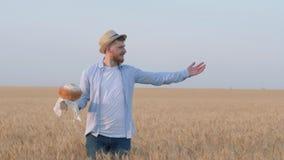 Oogstend, houdt de gelukkige kerel brood in zijn hand en toont met handuitgestrektheid van het gebied van de korreltarwe in het s stock video