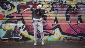 Сool girl dancing on the background of graffiti. stock footage