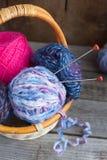 Oolen débobine pour tricoter avec des pointeaux de tricotage dans un panier Photo stock