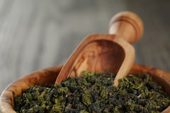 Oolong green tea in olive bowl. On oak table Royalty Free Stock Photo