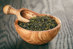 Oolong green tea in wood bowl on oak table Royalty Free Stock Images