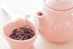 Oolong tea in ceramic cup, jar and wooden spoon Stock Image