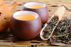 Oolong tea. Cups of chinese oolong tea and dried leaves on bamboo mat background Stock Images