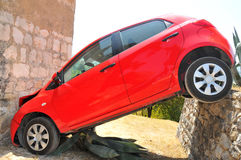 Ooops. A small red car driven over a wall and crashed into the wall of a church, then wedged at an angle Royalty Free Stock Photo