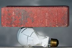 Oops!. Light bulb being crushed by falling brick Royalty Free Stock Photos
