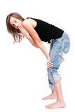 Oops!. Young girl i ragged jeans bending forward with shocked facial expression Stock Image