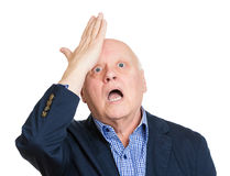 Oops, duh. Closeup portrait, goofy, funny face, senior mature man slapping hand on head to say duh, oops, isolated white background. Negative human emotion Stock Photos
